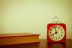 Despertador e livro vermelhos na tabela com fundo branco da parede - v Imagens de Stock