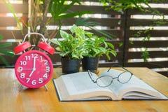 Despertador e livros vermelhos do vintage na tabela de madeira Fotos de Stock Royalty Free