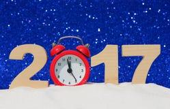 Despertador e os números 2017 em um monte de neve em um fundo azul do brilho Foto de Stock