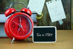 Despertador e quadro-negro vermelhos na tabela de madeira Fotografia de Stock