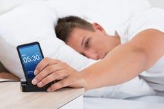 Despertador el dormitar del hombre en el teléfono celular Imagen de archivo