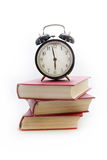 Despertador em uma pilha dos livros Imagens de Stock Royalty Free