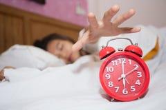 Despertador en dormitorio con intentar perezoso el dormir de la mujer parar foto de archivo libre de regalías