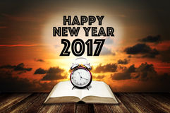 Despertador en el libro abierto con el saludo de la Feliz Año Nuevo Imagen de archivo