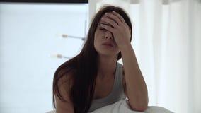 Despertador en el teléfono Mujer cansada que despierta en cama en el dormitorio metrajes