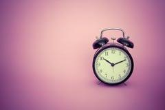 Despertador en fondo rosado Imagen de archivo