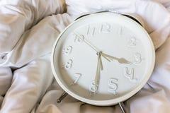 Despertador en la manta sucia de la arruga Foto de archivo libre de regalías
