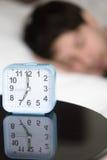 Despertador en la tabla delante del hombre durmiente, vertical imagen de archivo libre de regalías