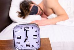 Despertador en sueño barbudo sin afeitar soñoliento de la cara del hombre de la mesita de noche en fondo de la máscara de ojo Hom fotos de archivo libres de regalías