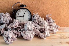 Despertador en un concepto del papel usado para una pérdida del tiempo de tiempo Imagenes de archivo