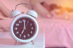 despertador na cama no quarto Foto de Stock Royalty Free