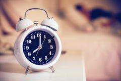 despertador na cama no quarto, estilo retro Fotografia de Stock Royalty Free