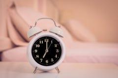 despertador na cama no quarto, estilo retro Imagens de Stock Royalty Free