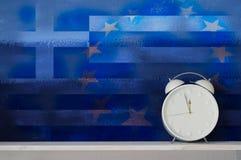 Despertador na frente da parede pintada de Grécia e da União Europeia Imagens de Stock Royalty Free