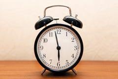 Despertador na tabela de cabeceira na sala Fotografia de Stock Royalty Free