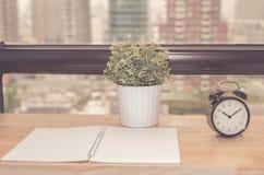 Despertador na tabela de trabalho no tom do vintage da opinião da cidade do escritório imagens de stock royalty free