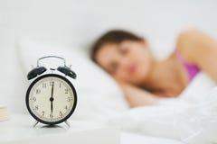 Despertador na tabela e na mulher no fundo fotos de stock royalty free