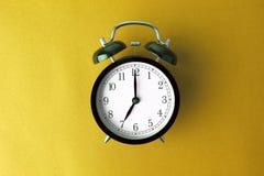 Despertador negro del vintage en fondo amarillo del color Fotografía de archivo