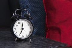 Despertador preto em um guardanapo listrado preto e branco que mostra a 7 o o& x27; pulso de disparo em uma tabela de cabeceira Imagem de Stock