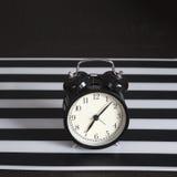 Despertador preto em um guardanapo listrado preto e branco que mostra a 7 o o& x27; pulso de disparo em uma tabela de cabeceira Foto de Stock Royalty Free