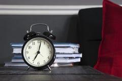 Despertador preto em um guardanapo listrado preto e branco que mostra a 7 o o& x27; pulso de disparo em uma tabela de cabeceira Fotos de Stock Royalty Free
