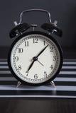 Despertador preto em um guardanapo listrado preto e branco que mostra a 7 o o& x27; pulso de disparo em uma tabela de cabeceira Imagens de Stock Royalty Free
