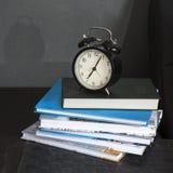 Despertador preto em um guardanapo listrado preto e branco que mostra a 7 o o& x27; pulso de disparo em uma tabela de cabeceira Imagem de Stock Royalty Free