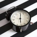 Despertador preto em um guardanapo listrado preto e branco que mostra a 7 o o& x27; pulso de disparo em uma tabela de cabeceira Imagens de Stock