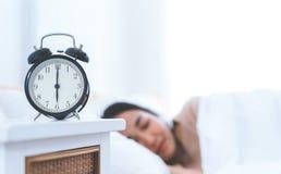 Despertador que cuenta a seis con la mujer todavía que duerme adentro Fotografía de archivo