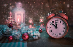 Despertador que muestra cinco a doce y el arreglo del invierno Foto de archivo libre de regalías