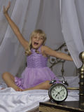 Despertador que se coloca en la mesita de noche Despierte de una chica joven dormida está estirando en cama en fondo Imagen de archivo