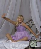 Despertador que se coloca en la mesita de noche Despierte de una chica joven dormida está estirando en cama en fondo Foto de archivo libre de regalías