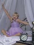 Despertador que se coloca en la mesita de noche Despierte de una chica joven dormida está estirando en cama en fondo Imagenes de archivo