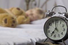 Despertador que se coloca en la mesita de noche Despierte de una chica joven dormida que para el despertador en una cama por la m Foto de archivo libre de regalías