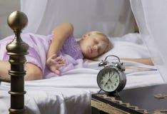 Despertador que se coloca en la mesita de noche Despierte de una chica joven dormida que para el despertador en una cama por la m Fotografía de archivo