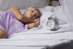 Despertador que se coloca en la mesita de noche Despierte de una chica joven dormida que para el despertador en una cama por la m Foto de archivo