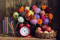Despertador, ramalhete, maçãs na cesta e livros na tabela r Imagens de Stock