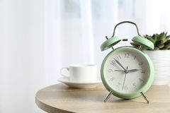 Despertador retro bonito com xícara de café e a planta suculento na tabela foto de stock