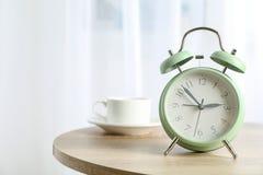 Despertador retro bonito com a xícara de café na tabela imagem de stock royalty free