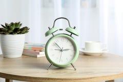 Despertador retro bonito com xícara de café, a planta suculento e os livros na tabela imagem de stock