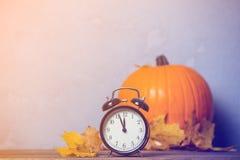 Despertador retro com as folhas com a abóbora no fundo Foto de Stock Royalty Free