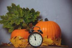 Despertador retro com as folhas com a abóbora no fundo Imagens de Stock