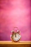 Despertador retro com dois minutos à meia-noite Foto filtrada nas cores vibrantes 50s a 60s Fundo cor-de-rosa Foto de Stock