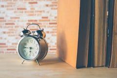 Despertador retro con el libro de la fila en la tabla de madera Fotografía de archivo libre de regalías