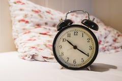Despertador retro con el reloj del ` de 10 O y el minué veinte, en la cama blanca con la almohada Foto de archivo