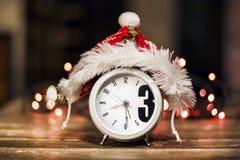 Despertador retro con el sombrero rojo de la Navidad Fotos de archivo