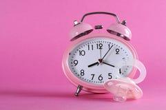 Despertador retro del estilo del vintage bastante rosado con el pacificer del maniquí del bebé fotografía de archivo