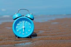 Despertador retro en la arena de la playa del mar Imagenes de archivo