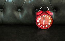 Despertador retro rojo en el sofá oscuro Fotografía de archivo