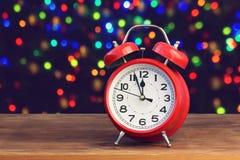 Despertador retro vermelho doze no o& x27; pulso de disparo no fundo com b Foto de Stock Royalty Free